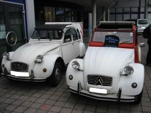 ein ganz cooles altes Auto und noch ein cooleres aelteres Auto stehen nebeneinander - beide sind Enten