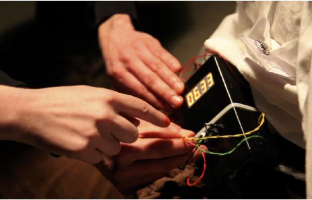 Hände mehrer Menschen, die gemeinsam eine Bombe entschärfen