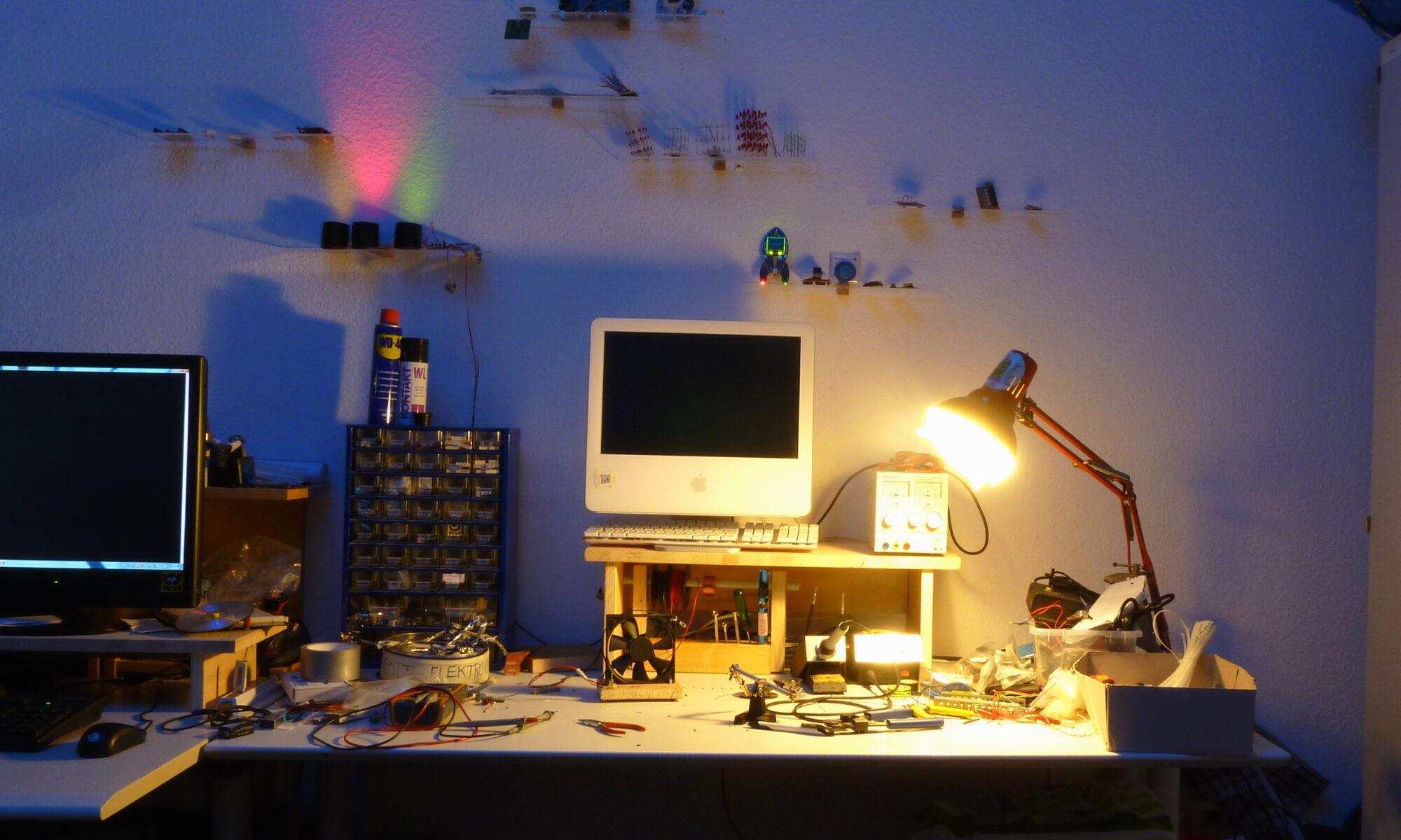 Ein Tisch mit Lötkolben und elektronischen Bauteilen, beleuchtet von einer kleinen Schreibtischlampe. Ein alter iMac thront über dem Chaos. An der Wand gibt es eine Ausstellung aus winzigen Projekten und farbige Leuchtdioden.